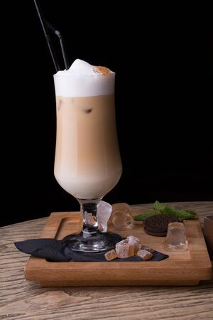 Milky coffee beverage in a high glass with a straw