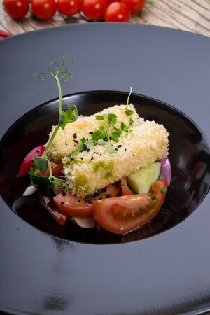 Fried cheese starter served with vegetable salad