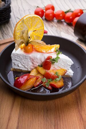 Slice of cheese cake decorated with berries and peaches 写真素材