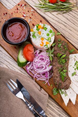 Grilled lamb kebab served with rice garnish and vegetables on a wooden board 写真素材