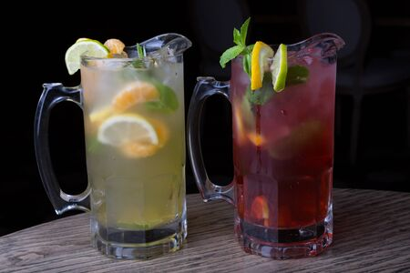 Glass pitchers of fresh cold icy lemonade drinks