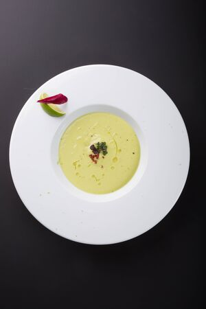 Green creamy avocado soup with lime in white bowl plate