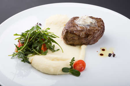Fried beef steak served with mashed potatoes and arugula