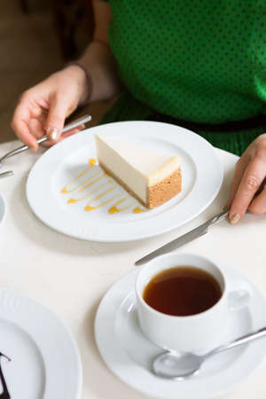 Woman eating cheese cake with cup of tea in a cafe