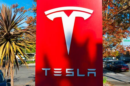 Tesla sign and logo at American automotive and energy company dealership