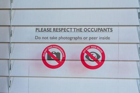 Sign prohibiting taking pictures and peering inside of the windows with closed shutters notifies visitors and tourists that photography is not allowed. Stockfoto