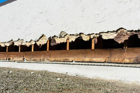 Roof to wall stucco step flashing replacement. Stucco sidewall and flat roof joint with removed stucco, exposed wall studs, underlying and wire.