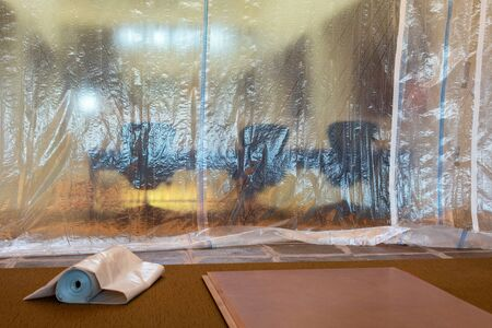 Plastic drop cloth hangs from ceiling to carpet floor to protect furniture from spills, paint drips and splatter, dust management, and debris during painting, demolishing or construction.