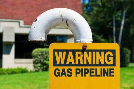 Gas pipeline warning sign on white bended pipe with blurred background of green landscape and commercial office building. Imagens