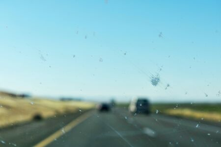Dirty car window glass with insects and dirt affect driver visibility while driving on divided highway. The worn out or bad car wiper blades smear dead bugs and dirt all over windshield. Zdjęcie Seryjne