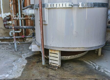 Water heater leaks from the bottom to the floor. Overflowing water heater drip pan. It is time to call a plumber service for inspection, repair or replacement.