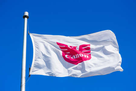 Canon flag proudly flying waving in the wind under blue skies at Canon Solutions America headquarters campus in Silicon Valley - San Jose, California, USA - 2020