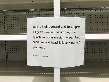 Sign informing customers that store places purchasing limits on some products as people fear the coronavirus outbreak spreading. Empty shelves in supermarket.