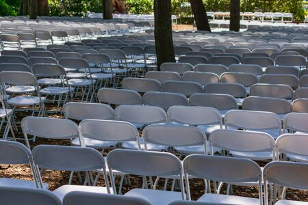 White plastic chairs set up an outdoor in a row before ceremony, event or party.