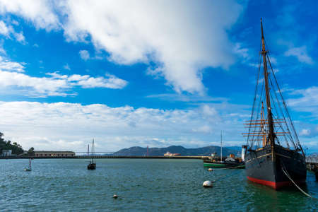 Scenic view of Aquatic Park under blue and cloudy sky. Moored historic ships preserved by Maritime National Historical Park - San Francisco, California, USA - December, 2019 Editorial