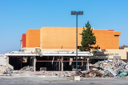 Partially demolished large commercial business property with exposed lower floor. Pile of demolition construction debris is ready for haul away service.