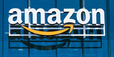 Amazon logo with its signature orange smile reflected in the glass facade of modern company campus - Palo Alto, California, USA - 2019