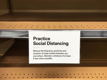 Practice Social Distancing sign one the empty shelves in a supermarket requesting customers to maintain a distance of at least 6 feet in order to prevent spread of a highly contagious disease COVID-19