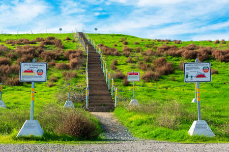 Hiking trail stairs lead to the top of the green hill that covers former landfill - Sunnyvale, CA, USA - January, 2020 Éditoriale