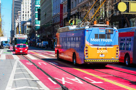 Muni electric trolley buses and taxi navigate red transit only lanes to ride passengers in car free zone of Market Street in downtown - San Francisco, California, USA - February, 2020