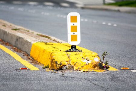 Dividing median curb on road with white and yellow warning reflecting sign on pole. Yellow traffic marking paint an overgrown vegetation