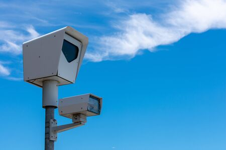 Red light camera. Close up. Traffic enforcement camera. Background blue sky with light clouds during day time.
