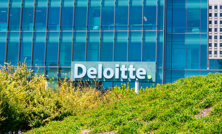 Deloitte logo is seen above green landscaping on company office downtown. Deloitte is one of the Big Four accounting organizations - San Francisco, California, USA - July 27, 2019