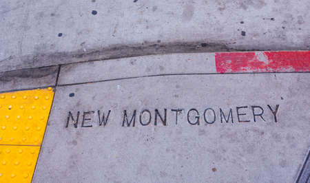 New Montgomery street name sign stamped on a sidewalk in downtown San Francisco. Yellow ADA compliant tactile paving. Weathered red paint on curb. Little black gum dots on concrete sidewalk. Editorial