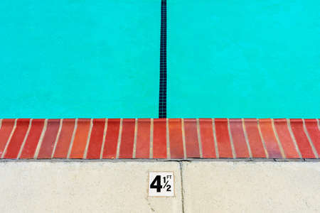 Swimming pool depth marker identifies the water depth for swimmers. Four and one half feet depth sign.