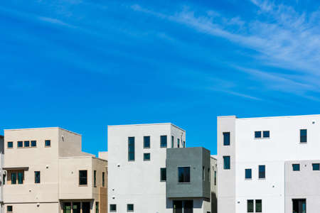 Exterior view of typical new multifamily low-rise residential row building under beautiful blue sky Foto de archivo