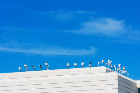 Various outside security cameras cover multiple angles from the rooftop of modern office building under blue sky