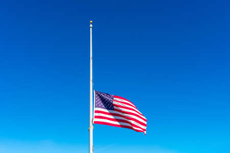 Flag of the United States flying at half staff waving in the wind under blue sky.