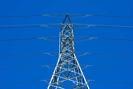 High voltage transmission tower (power tower, electricity pylon, steel lattice tower) with parallel single-circuit lines in the blue sky