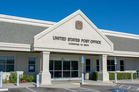 Entrance exterior of United States Post Office on sunny day with clear blue sky - Cupertino, California, USA - 2018