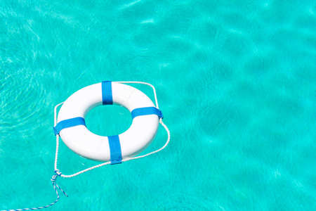 Foam ring pool buoy with nylon tow rope surround on swimming pool water. Foto de archivo
