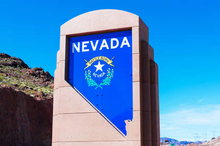 Welcome to Nevada monument sign along highway 11. The concrete plinth featuring recessed state silhouette with bold white lettering and the Nevada crest - Boulder City, Nevada, USA - 2020