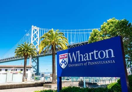 Wharton University of Pennsylvania sign near school campus with San Francisco Oakland Bay Bridge in background - San Francisco, California, USA - 2019 Editorial