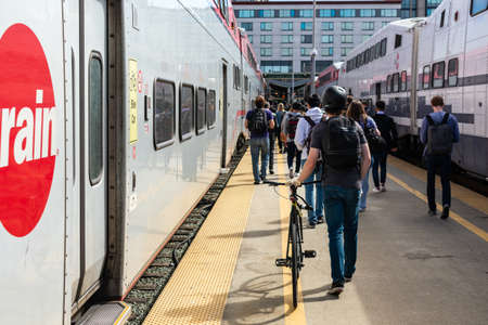 Crowd of passengers walking on outdoor train platform toward station exit after disembarking Caltrain cars at commuter rail line terminus - San Francisco, California, USA - 2019