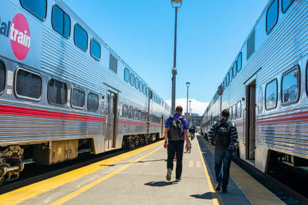 Passengers walking on outdoor train platform to board Caltrain car at commuter rail line terminus during day time - San Francisco, California, USA - 2019