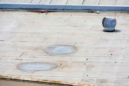 Ponding water on the settled flat roof. Turbine vent on the flat roof in an industrial building.