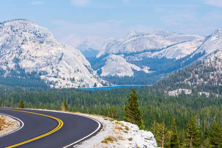 Empty Tioga Pass road running through Sierra Nevada mountain scenery on sunny day in summer near Olmsted Point in Yosemite National Park.