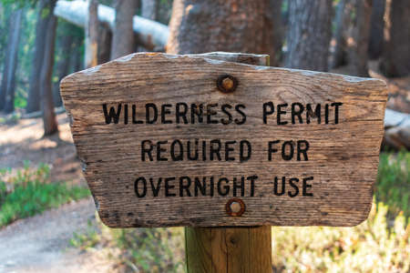 Wilderness permit required for overnight use sign on the wooden post in the national forest. Foto de archivo