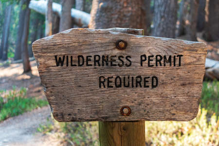 Wilderness permit required sign on the wooden post in the national forest.