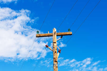 Weathered wooden utility pole with parallel single-circuit lines and colorful isolators in the blue sky.