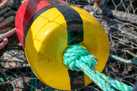 Close up of red and yellow floating buoys used for commercial crab fishing