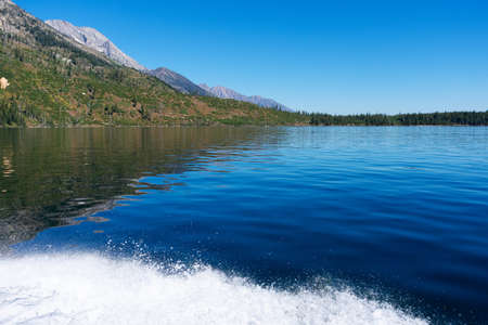 Splashing water from a speed boat on a calm blue lake. Beautiful mountain range in the background on a sunny summer day. Foto de archivo