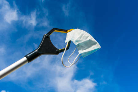 Reach extender holds a used disposable surgical mask against the clouds and blue sky. Foto de archivo