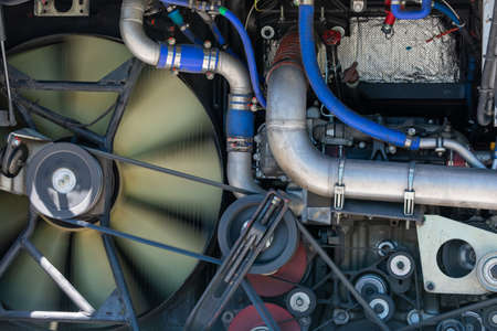 Close up view on working bus, truck diesel engine with rotating fan, motor belt, pulley, gear, engine equipment details. Assembled bus, truck diesel engine. Abstract automotive industrial background.
