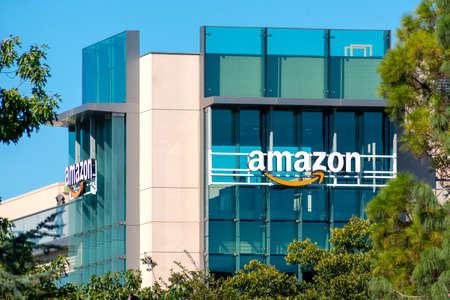Amazon office building facade surrounded by green trees under blue sky - Palo Alto, California, USA - 2020