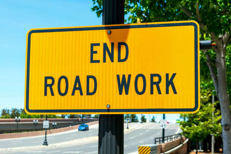End Road Work traffic sign. Background wide urban street with a few cars. Foto de archivo